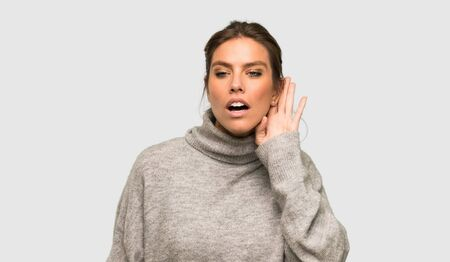 Blonde woman with turtleneck listening to something by putting hand on the ear over isolated grey background