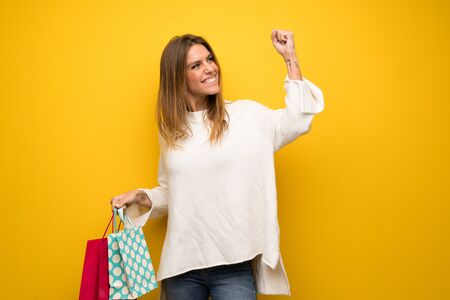 Blonde woman over yellow wall holding a lot of shopping bags in victory position