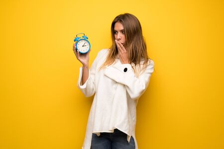 Blonde woman over yellow wall holding vintage alarm clock