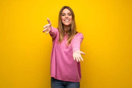 Woman with pink sweater over yellow wall presenting and inviting to come with hand Stock Photo