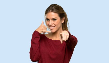 Blonde woman making phone gesture and pointing front over isolated blue background 写真素材