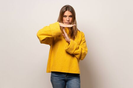 Woman with yellow sweater over isolated wall making time out gesture