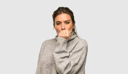Blonde woman with turtleneck having doubts over isolated grey background