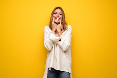 Blonde woman over yellow wall smiling with a happy and pleasant expression