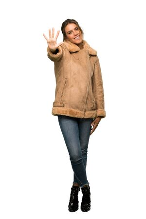 A full-length shot of a Blonde woman with a coat counting five with fingers over isolated white background