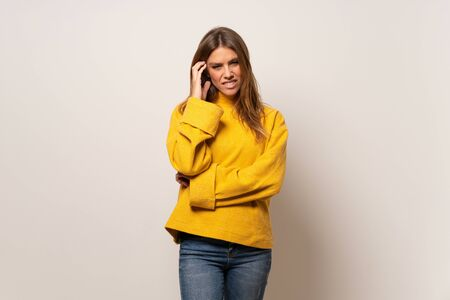 Woman with yellow sweater over isolated wall having doubts Stock fotó