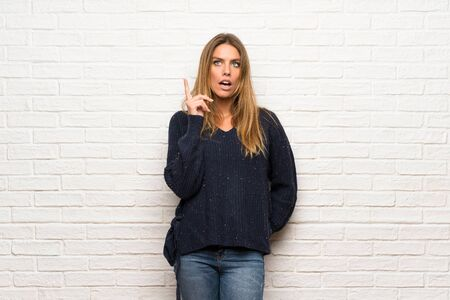 Blonde woman over brick wall thinking an idea while scratching head