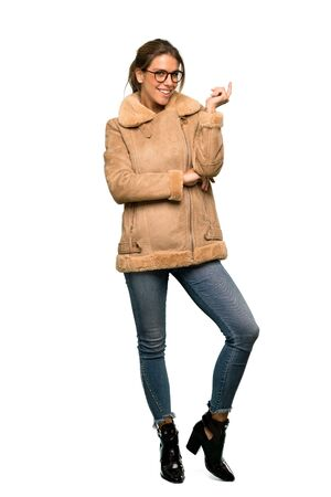 A full-length shot of a Blonde woman with a coat with glasses and smiling over isolated white background Imagens