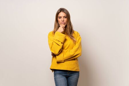 Woman with yellow sweater over isolated wall thinking