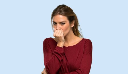 Blonde woman having doubts over isolated blue background