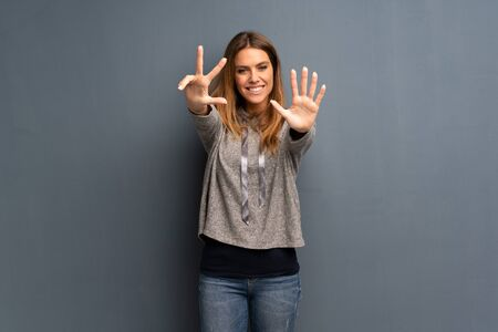 Blonde woman over grey background counting eight with fingers