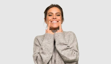 Blonde woman with turtleneck smiling with a happy and pleasant expression over isolated grey background Stok Fotoğraf