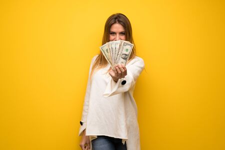 Blonde woman over yellow wall taking a lot of money