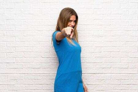 Woman with blue dress over brick wall points finger at you with a confident expression