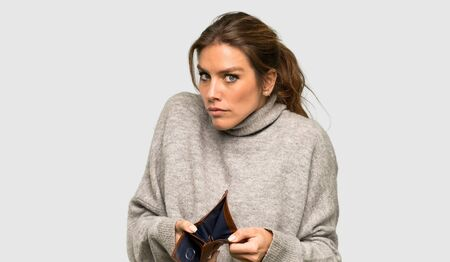 Blonde woman with turtleneck holding a wallet over isolated grey background