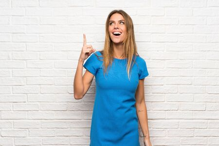 Woman with blue dress over brick wall intending to realizes the solution while lifting a finger up 写真素材
