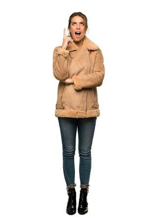Una foto a figura intera di una donna bionda con un cappotto che punta con il dito indice una grande idea su sfondo bianco isolato