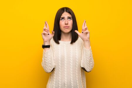 Young woman over isolated yellow wall with fingers crossing and wishing the best 스톡 콘텐츠