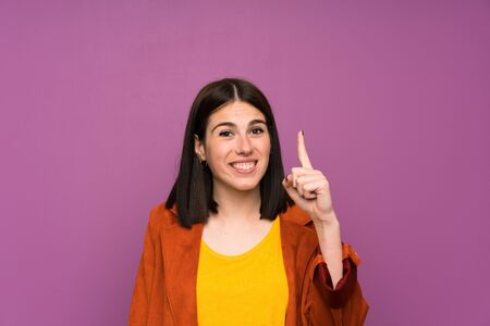 Young woman with a coat over isolated purple background pointing with the index finger a great idea 写真素材