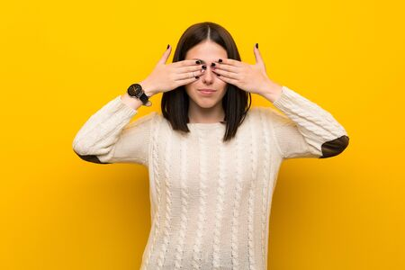 Young woman over isolated yellow wall covering eyes by hands Фото со стока