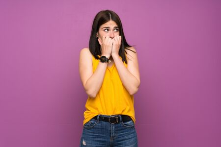 Young woman over isolated purple wall nervous and scared putting hands to mouth Imagens