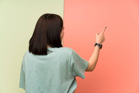 Young woman over isolated colorful wall pointing back with the index finger 写真素材