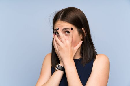 Young woman over isolated blue wall covering eyes and looking through fingers