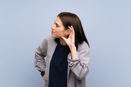 Young woman over isolated blue wall listening to something by putting hand on the ear