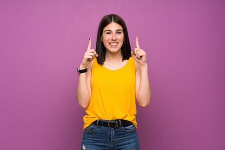 Young woman over isolated purple wall pointing up a great idea
