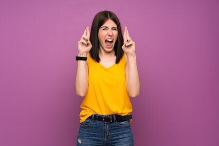 Young woman over isolated purple wall with fingers crossing