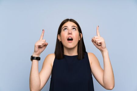 Young woman over isolated blue wall pointing with the index finger a great idea