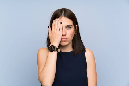 Young woman over isolated blue wall covering a eye by hand Фото со стока