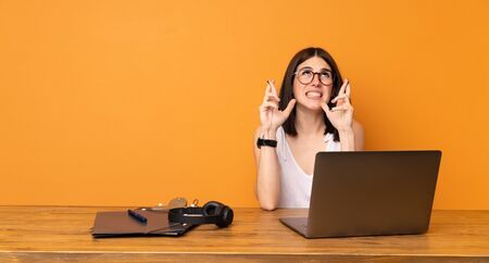 Business woman in a office with fingers crossing and wishing the best