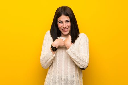 Young woman over isolated yellow wall with surprise facial expression