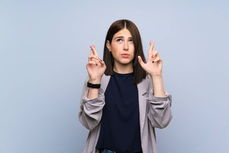 Young woman over isolated blue wall with fingers crossing and wishing the best 스톡 콘텐츠