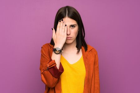 Young woman with a coat over isolated purple background covering a eye by hand
