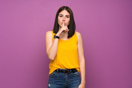 Young woman over isolated purple wall showing a sign of silence gesture putting finger in mouth