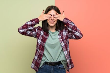 Young woman over isolated colorful wall covering eyes by hands