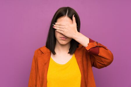 Young woman with a coat over isolated purple background covering eyes by hands Фото со стока