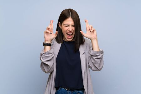 Young woman over isolated blue wall with fingers crossing