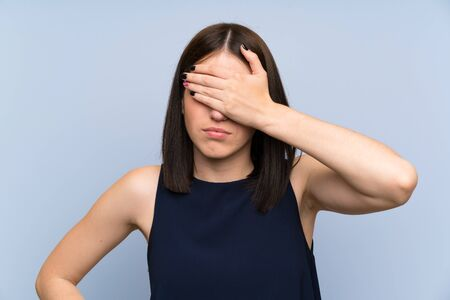 Young woman over isolated blue wall covering eyes by hands