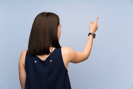 Young woman over isolated blue wall pointing back with the index finger 写真素材
