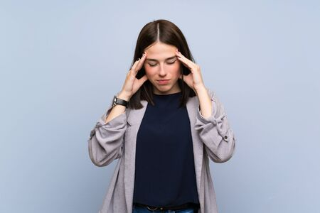 Young woman over isolated blue wall with headache