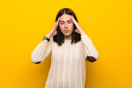 Young woman over isolated yellow wall with headache