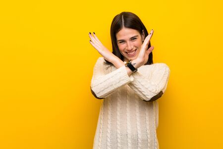 Young woman over isolated yellow wall making NO gesture