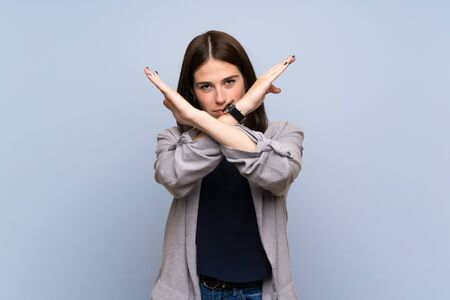 Young woman over isolated blue wall making NO gesture