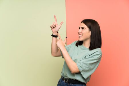 Young woman over isolated colorful wall pointing with the index finger a great idea 写真素材