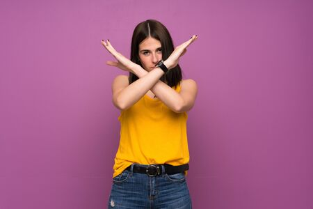Young woman over isolated purple wall making NO gesture Stockfoto