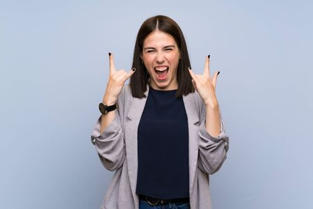Young woman over isolated blue wall making rock gesture