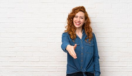 Redhead woman over white brick wall shaking hands for closing a good deal Stockfoto